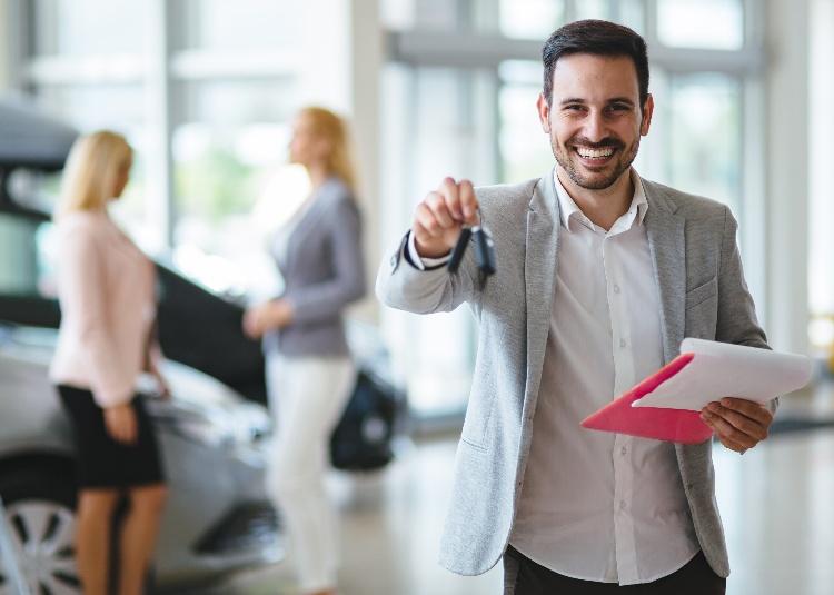 Un vendeur tend des clés de voiture à son nouveau propriétaire